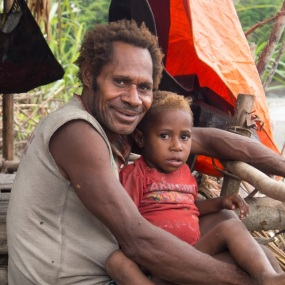 Jungle, Indonesia - January 13, 2015: A man from the Korowaya tribe with a child on his lap, sitting on the bank of the river fishing